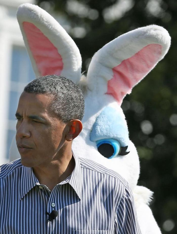 President Barack Obama stands in front of the Easter Bunny while he participates in the annual Easter Egg Roll on the White House